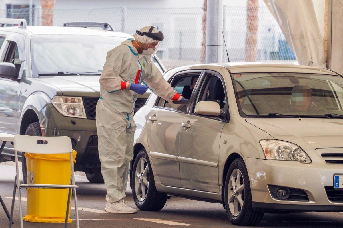 Un enfermero de Atención Primaria de Tenerife realiza la toma de muestras a una familia de la capital en su vehículo.   S.M.